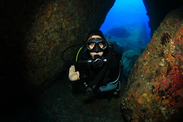 Young woman scuba diver in underwater cavern