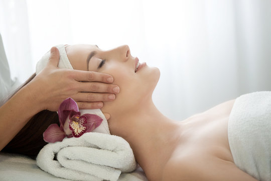 Spa salon: Young Beautiful Woman Having Facial Massage .