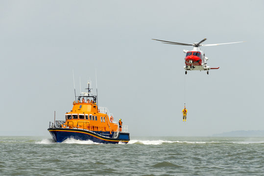 Orange sea rescue boat with rescue helicopter
