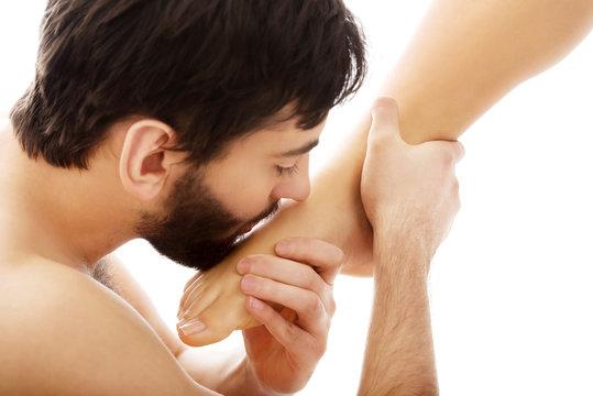 Handsome man kissing woman's feet.