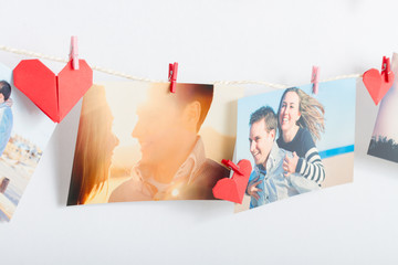 Photos hanging on clothesline with origami hearts