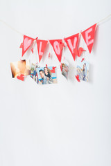 Wall with pictures and garland hanging on clothesline