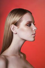 Портрет блондинки на красном фоне с длинными волосами