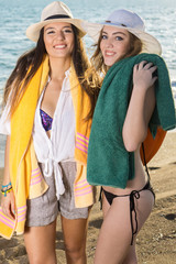 Smiling Girls with their Towels at the Beach.