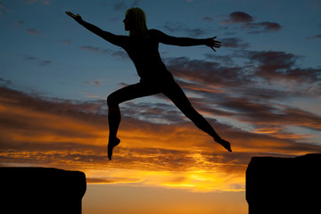 silhouette of a woman jumping arms out
