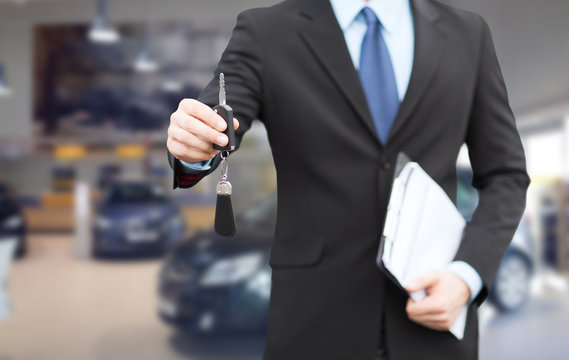close up of businessman or salesman giving car key