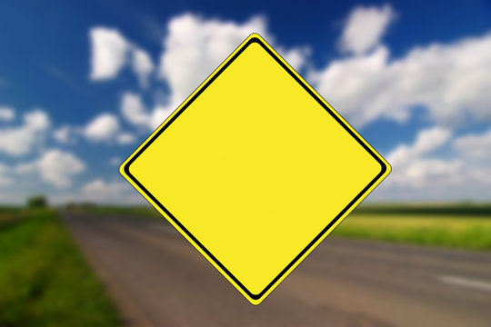 Empty road with yellow traffic sign