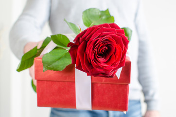 Man holding a gift and a red rose