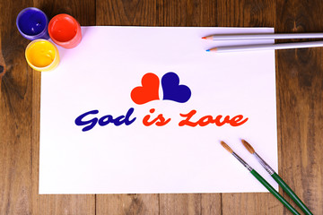 God is Love text on paper on wooden table background