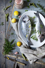 preparation of two fresh bream with herbal seasoning and lemon
