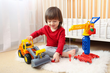lovely toddler boy plays cars at home