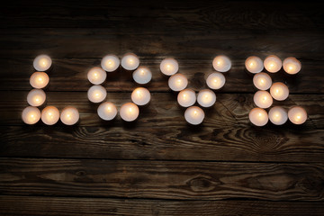 inscription love from candles on wooden background