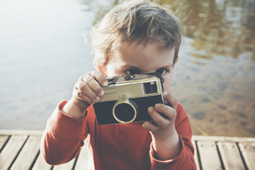 Portrait of a smiling cute boy taking picture with retro camera