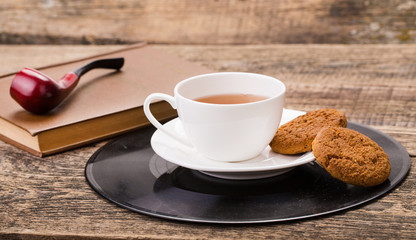 ivory tea cup with sweet cookie, book and tobacco pipe on wooden