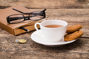 ivory tea cup with sweet cookie, glasses, money and book on wood