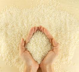 Hand hold Thai jasmine rice grain on wooden