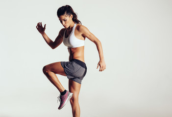 Attractive fit woman exercising in studio with copyspace