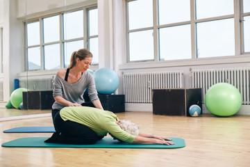 Female trainer helping senior woman doing yoga