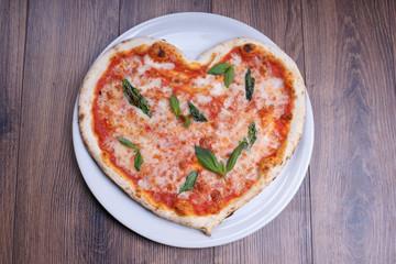 Пицца в виде сердца на тарелке на деревянном столе