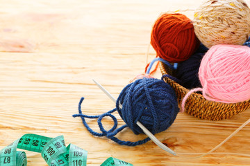 balls of yarn and knitting needles on board