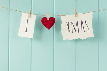 """I love xmas"" hanging on a rope with clothespins."