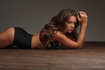 hot sexy girl lying on the wooden floor in black lingerie