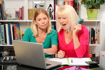 Senior woman and caregiver with laptop and credit card
