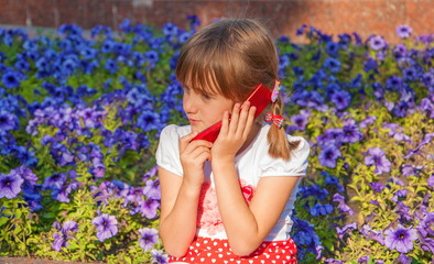Little girl talking on cell phone on background of flowers