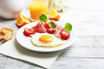 Bacon and eggs on color wooden table background.