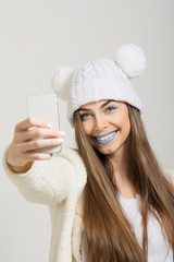 Fashion model in winter style taking a selfie with smartphone