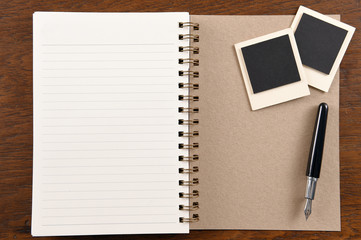 Blank notebook with pen and photo frames on wooden background.