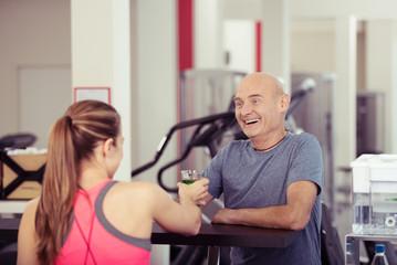 älterer mann nimmt ein getränk im fitness-studio