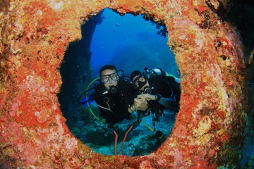 Scuba diving couple framed by coral Wall mural