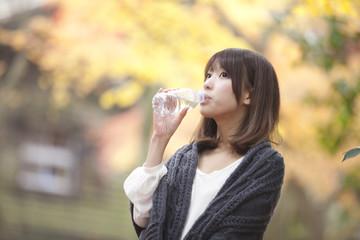 秋の紅葉した公園で立って水を飲んでいる女性
