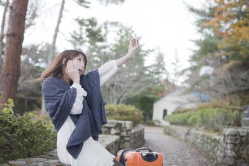 秋の石畳にトランクを置いて写真を撮っている笑顔の女性