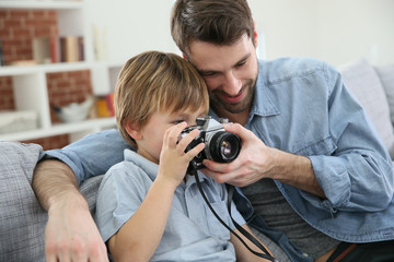 Daddy with son using photo camera