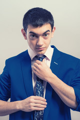 Handsome guy straightens his tie in the background