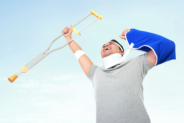 cheerful injured young man hold up the crutch