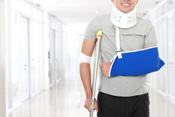 injured young man use crutch and arm sling