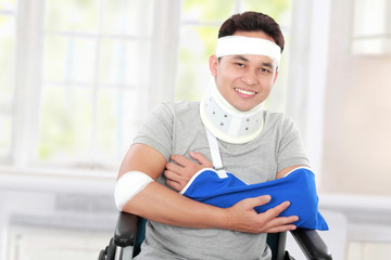 injured young man in wheelchair with cross arm