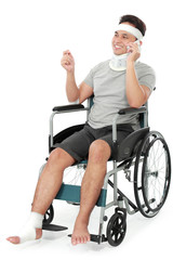 injured young man in wheelchair talking on the phone