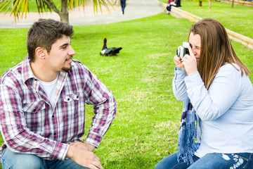 Young woman doing a photo to her boyfriend in the park