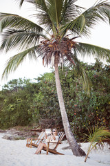 Woman relaxing under palm and making photos with pad