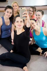 Group of beautiful sporty girls taking selfie, self-portrait wit
