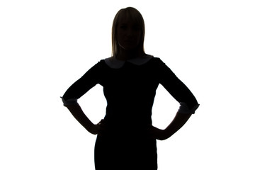 Silhouette of young woman with hands on hip