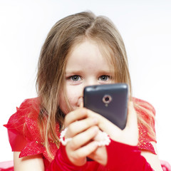 Cute little girl dressed in ball gown playing with smartphone