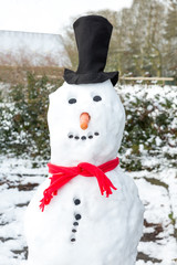 Snowman wearing black hat and red shawl