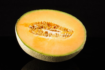 Cantaloupe melon fruit with reflection on the black background