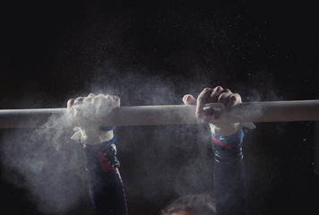 Poster Gymnastiek hands of gymnast with chalk on uneven bars