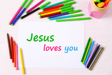 Jesus loves you text on paper on table background